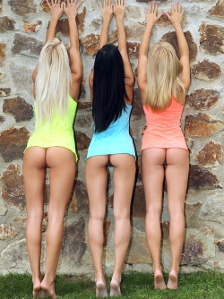 Three Cute and Petite Models Strip off Their Colorful Shirts by the Wall